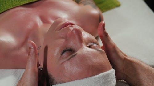 Hands of Professional Masseurin Massage Frauengesicht in Beauty Saloon