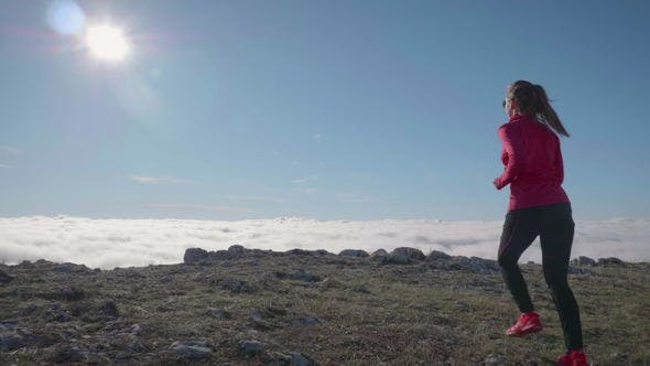 Thumbnail for Young Caucasian Woman in Sunglasses Is Jogging in Mountains Above Clouds at Sunny Day. Sky Running