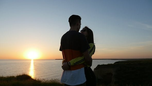 Cover Image for Sweet Girl and Her Emotional Boyfriend at the Black Sea Coast at Sunset in Summer