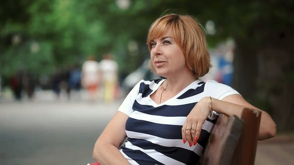 Thumbnail for Beautiful Blond Woman Sits on a Bench and Looks Around in a Park in Summer