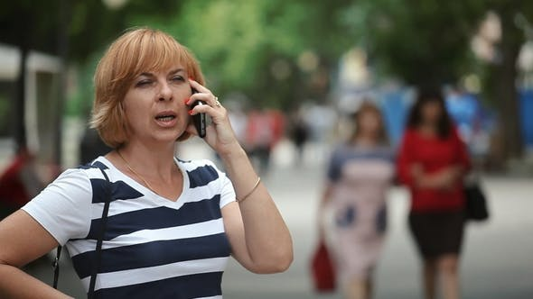 Thumbnail for Confident Blond Woman Is Talking on Phone with Her Partner in a Street in Summer