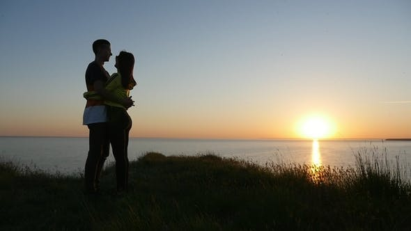 Cover Image for Tender Girl and Her Happy Boy Are at the Black Sea Coast at Sunset in Summer