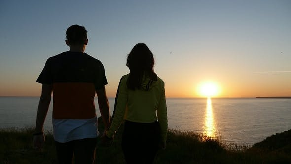 Thumbnail for Lovely Boy and Girl Walk Along the Black Sea Coast at Sunset in