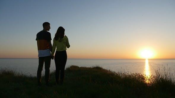 Thumbnail for Amorous Boy and Girl Stand and Talk  on the Black Sea Coast at Sunset