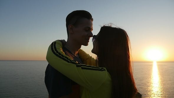 Thumbnail for Amorous Girl Hugs Her Happy Boy at the Black Sea Coast at Sunset in Summer
