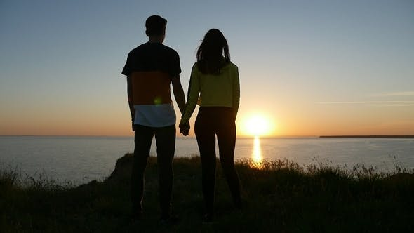 Cover Image for Enamored Boy and Girl Stand on the Black Sea Coast and Enjoy the Sunset