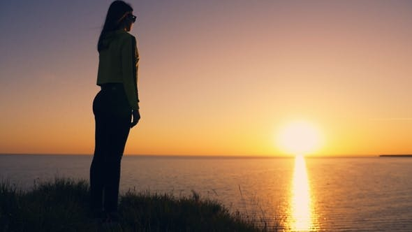 Cover Image for Emotional Girl Stands on the Black Sea Coast and Looks at the Shining  Sunset