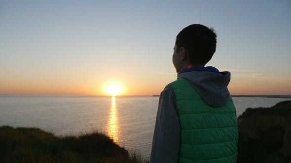 Cover Image for Romantic Boy Stands on the Black Sea Coast and Looks at the Wonderful Sunset