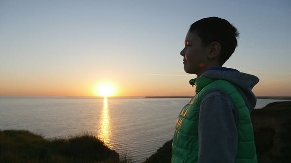 Thumbnail for Dreaming Boy Stands on the Black Sea Coast and Looks at the Sparkling Sunset