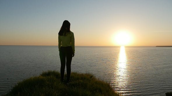 Thumbnail for Amorous Girl Stands on the Black Sea Shore and Looks at the Shining  Sunset