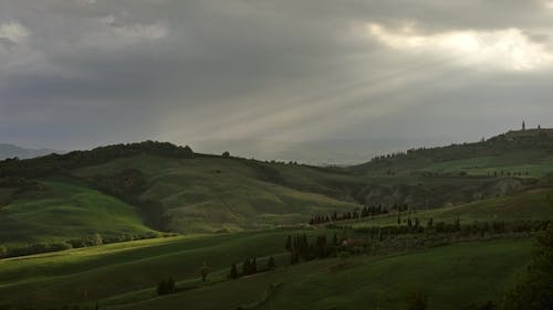 Ray of the Setting Sun Slips Over Hills of Tuscany