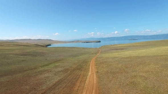 Thumbnail for Aerial View of Dirt Road to the Blue Water Coast on Sunny Day at Olkhon, Baikal Lake