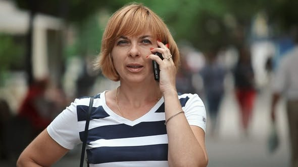 Cover Image for Smart Blond Woman Is Talking on Phone with Her Folks in a Street in Summer