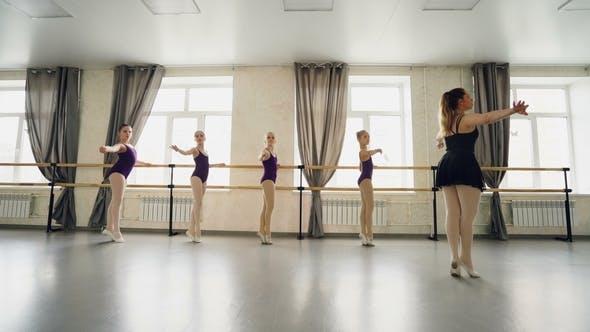 Professioneller Ballettlehrer bringt kleinen Mädchen bei, Zehenspitzen anzumachen und Beine und Arme zu strecken
