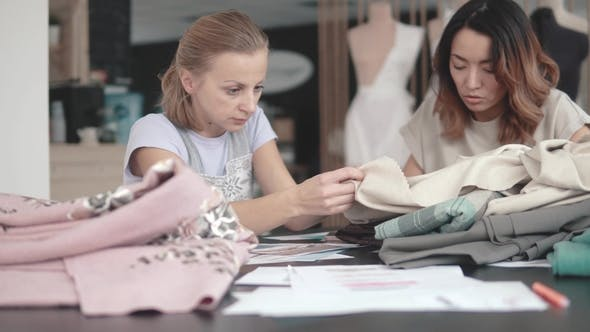 Thumbnail for Fashion Designers Choose Fabrics for Tailoring Two Seamstresses Work in the Atelier