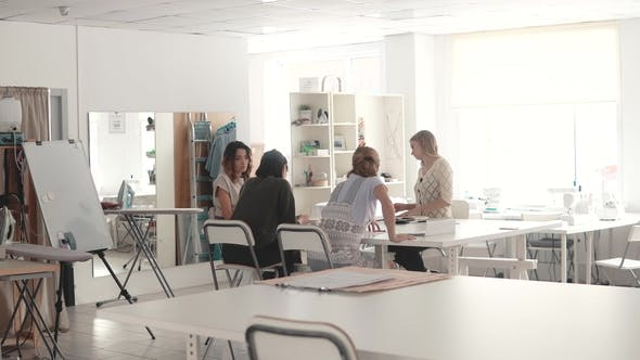 Cover Image for Fashion Designers in Small Business Startup Company Sit in the Atelier at Their Desk and Do Business