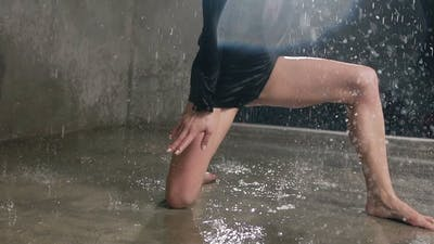 Young Dancer Girl in a Blacksuit Performs a Contemporary Dance with Under the Water Rain