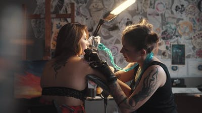 Master Tattoo Is Doing Tattoo in a Home Studio. Girl Tattooist Working Tattoo Machine in Home Studio