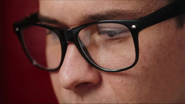 Thumbnail for of Man's Eyes in Glasses While He Works at the Laptop in Office