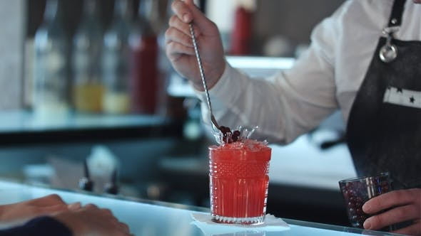 Thumbnail for Bartender Decorating Cocktail Red Alcoholic Cocktail with Berries