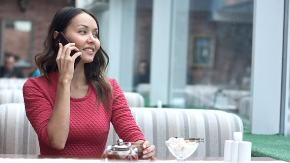 Thumbnail for Young Charming Woman Calling with Cell Telephone While Sitting Alone in Cafe
