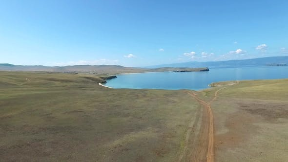 Thumbnail for Aerial View of Dirt Road To the Blue Water Coast on Sunny Day, Olkhon, Baikal Lake