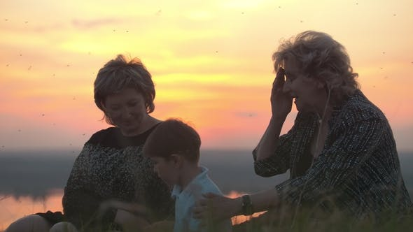 Thumbnail for Happy Family - Grandmother, Mother and Son Sitting on High Hill at Summer Sunset