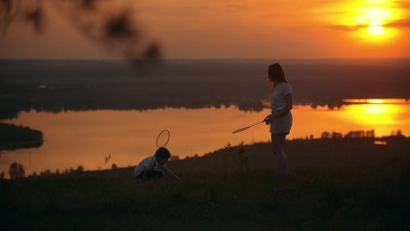 Thumbnail for Little Boy with His Older Sister Playing Badminton on the Hill at Sunset