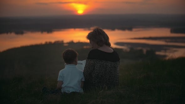 Thumbnail for Mother with Son Sitting on the Hill Reading a Book at Summer Sunset