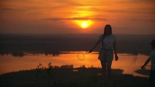 Young Woman Calling the Child To Play Badminton on the Hill at Simmer Sunset