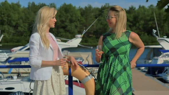 Thumbnail for Two Stylish Women Talk and Drink Champagne Standing at the Yacht Club Background