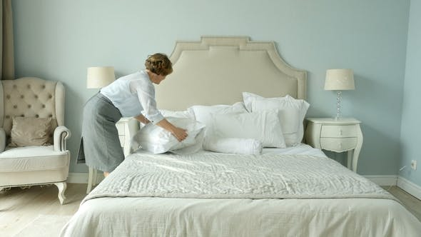 Thumbnail for Attractive Elderly Woman Makes The Bed In Bedroom