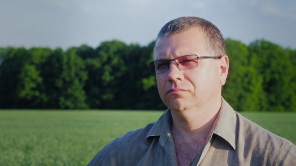 Thumbnail for Portrait of a Middle-aged Farmer in Glasses on the Background of a Green Field
