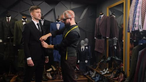 Stylish Tailor Dresses a Handsome Young Man in a Quality Handmade Suit in an Atelier. Creative Adult
