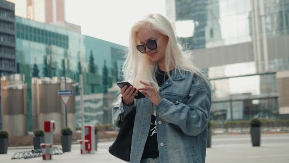 Thumbnail for Beautiful Woman Is Sending a Text Message Using an App on Her Smartphone While Walking in the Street