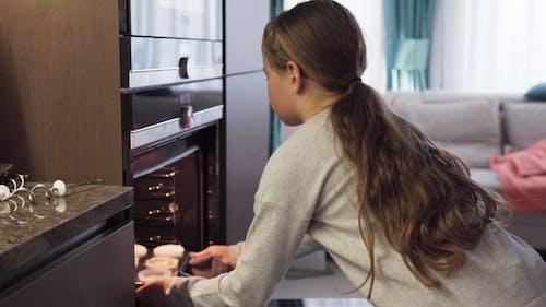 Mädchen setzt Cupcakes in Ofen zum Backen in Küche zu Hause