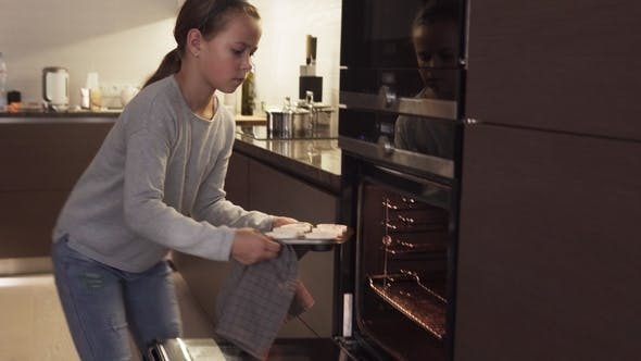 Thumbnail for Girl Puts Cookies in Oven for Baking in Modern Kitchen at Home