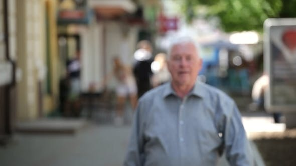 Thumbnail for Confident Grey-headed Man Goes in a Green Street on a Sunny Day in Summer