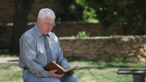 Old Codger Granddad in Glasses Sits and Reads in a Street in Summer