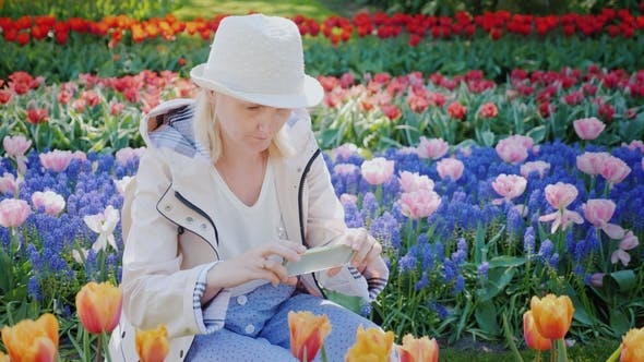 Thumbnail for Young Woman Tourist Taking Pictures of a Beautiful Flowerbed with Flowers in Keukenhof Park in the