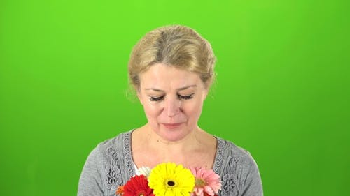 Woman Is Sniffing Flowers
