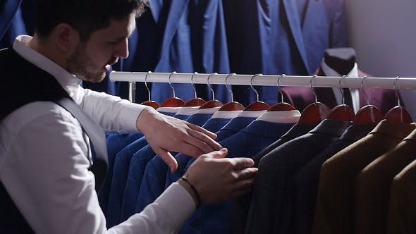 Young Man Choosing Classical Suit in the Suit Shop