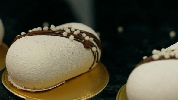 Thumbnail for White Pastries Lying in a Row and Being Decorated with Chocolate
