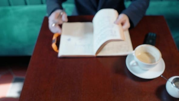 Thumbnail for Young Businessman Is Working with Notebook, Sitting at Table in Cafe Interior.