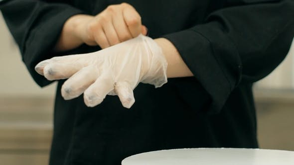 Thumbnail for of Female Cooker Putting White Gloves on Her Hands in the Kitchen