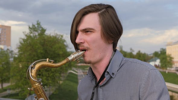 Thumbnail for Young Man Plays the Saxophone, . Man on the Background of the City's Landscape Blows Into the Pipe