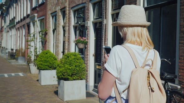 Cover Image for A Woman in a Hat and with a Backpack Walks Along the Narrow Street of the Ancient City of Delft in