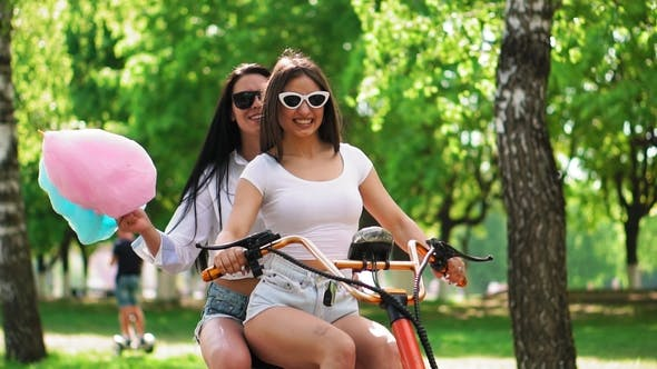 Thumbnail for Sexy Girls with Sweet Cotton in Short Shorts Ride an Electric Scooter in the Park