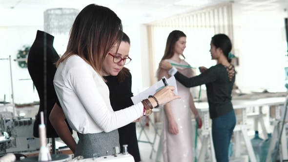 Thumbnail for Group of Dressmakers Work in the Atelier. Young Fashionable Designer Woman Talks To Her Assistant