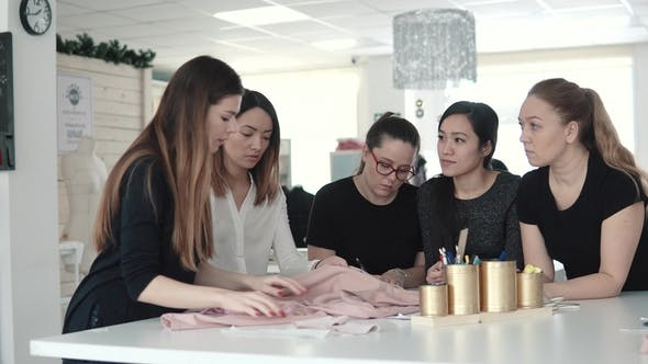 Thumbnail for Fashion Designer and His Assistants Choose Fabric for the Dress and Make Notes on Paper